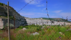 Old barbed wire around an abandoned limestone quarry. Stock Footage