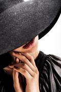 Beautiful woman with full lips in black hat poses on white background Stock Photos