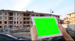 A woman holds a blank tablet PC with a green screen for your own custom conte Stock Footage