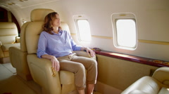 Wide view of woman passenger relaxing on private jet 4K - stock footage