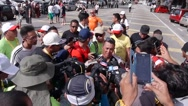Stock Video Footage of cyclist being interviewed by journalist and crowds