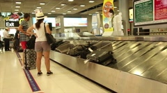 Wide shot passengers wait for their luggage at baggae claim after an internat Stock Footage