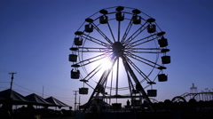 Ferris Whell silhouette. Amusement park. Sunset, blue sky Stock Footage