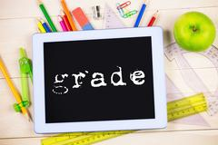 Grade against students table with school supplies - stock photo