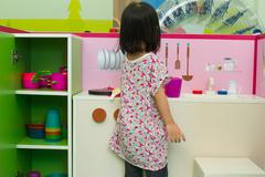 Chinese children role-playing at kitchen - stock photo