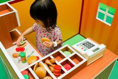 Chinese children role-playing at burger store. - stock photo