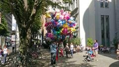 Man with bunch of balloons on alte potsdamer street in Berlin Stock Footage