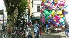 Man is selling balloons on alte potsdamer street in Berlin Stock Footage