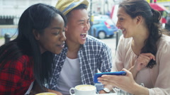 4k Happy group of friends looking at mobile phone at outdoor cafe Stock Footage