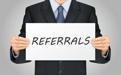 businessman holding referrals word poster - stock illustration