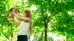 Girl with long hair playing with her beagle dog in park. Slow motion Stock Footage