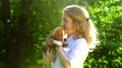 Beautiful woman playing with her beagle dog in park. Slow motion Stock Footage