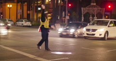 Traffic officer directing car traffic at intersection Hollywood Blvd La Brea Ave Stock Footage
