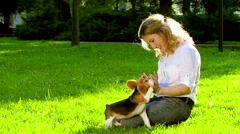 Girl playing with her beagle dog in  park. Slow motion Stock Footage