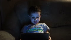 Child sits in a dark room and uses a tablet pc Stock Footage