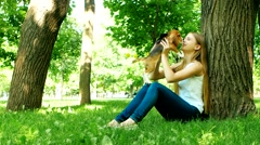 Girl playing with her beagle dog in summer park Stock Footage