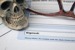Signature field on document with pen and skull signed here; document is mock- Stock Photos