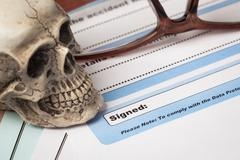 Signature field on document with pen and skull signed here; document is mock- - stock photo