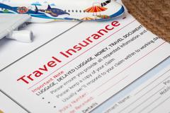 Travel Insurance Claim application form and hat with eyeglass on brown envelo Stock Photos