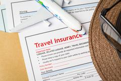 Stock Photo of Travel Insurance Claim application form and hat with eyeglass on brown envelo
