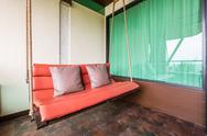 Stock Photo of swing sofa furnish, and leather pillow for decoration and relax at balcony