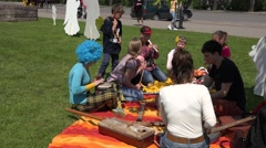 Children perform with various instruments on grass. 4K Stock Footage