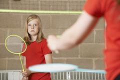 Two Girl Playing Badminton In School Gym - stock photo