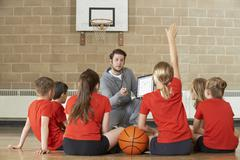 Coach Giving Team Talk To Elementary School Basketball Team Stock Photos