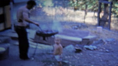 1973: Man grilling food outside trailer house for wife and baby. Stock Footage