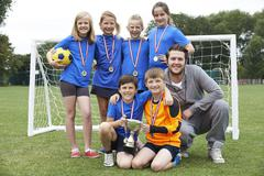 Victorious School Soccer Team With Medals And Trophy - stock photo