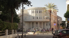 People sit outside Tel-Aviv old municipality building, white city architecture Stock Footage