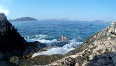Swimmer floats near the shore cliffs in the rough sea Stock Footage
