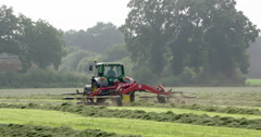 Agriculture tractor raking and haying Stock Footage