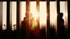 People silhouettes walking at sunset. Handheld shot - stock footage