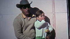 1974: Street kids hanging with dad and other children. - stock footage