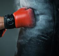 Hand  of boxer and punching bag over black background Stock Photos