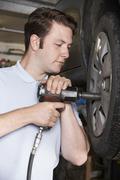 Mechanic In Garage Using Air Hammer On Car Wheel Stock Photos