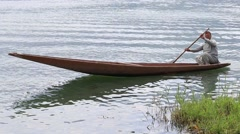 Local people use a small boat for transportation in the lake of Srinagar, India Stock Footage