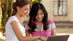 Two beautiful girls studying outdoors - stock footage