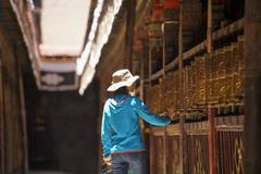 Stock Photo of Tourist touching prayer wheel in Jokhang Temple