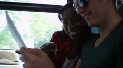 4k Happy attractive young man & woman using computer tablet on train journey - stock footage