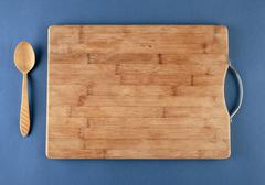 kitchen cutting board and a wooden spoon on a blue - stock photo