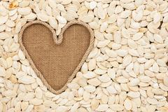 Symbolic heart made of rope lies on sackcloth and  pumpkin seeds - stock photo