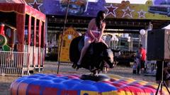 Girl riding mechanical bull at amusement park Stock Footage