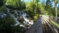 Movement along the parapet of wooden bridge in the alpine green forest Stock Footage
