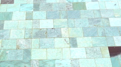 Detail of clear swimming pool with water and natural stone tile floor Stock Footage
