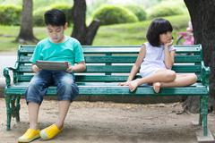 Stock Photo of Conflict between the Asian brother and sister sitting on a wooden bench in th