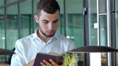 Young man in cafe reading a book - stock footage