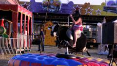 Girl riding mechanical bull at amusement park Stock Footage
