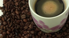 White coffee cup with coffee and around the cup lies coffee beans Stock Footage